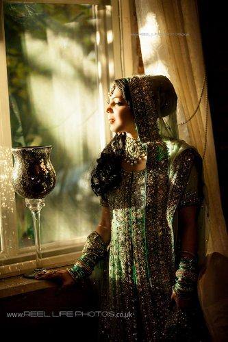 Magical sunlight on Asian bride's face by window